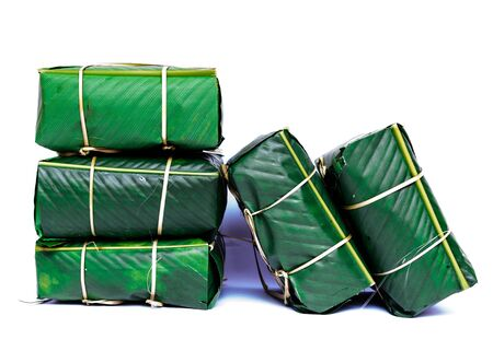 Pile of Chung Cakes isolated on white. Square glutinous sticky rice cake, stuffed with pork meat, green beans, wrapped tied in bamboo leaf and strings. Traditional Vietnamese New Year Tet food Stock fotó - 138200298