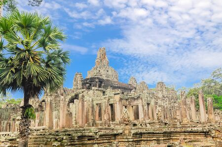 Ancient Angkor Wat temple and palm trees under summer cloud blue sky Banco de Imagens