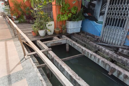 Variety of flower pots in front of residential house patio with boardwalk and under deck drainage along Malacca River, Malaysia. Remodel of deteriorated and new beams planks platform backwall Stockfoto