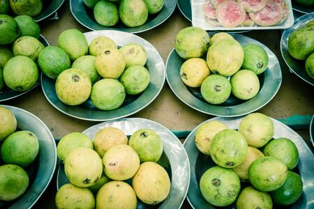 Pre-pack slices cut of red guavas and pile of fresh raw aluminium trays on display at local fruit stand in Little India. Organic and healthy tropical food at Singapore farmer market. Stockfoto