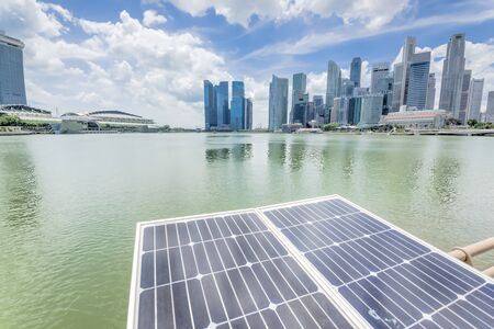 Close-up solar panel with modern city and skyscrapers in background in Singapore. Cloud blue sky.