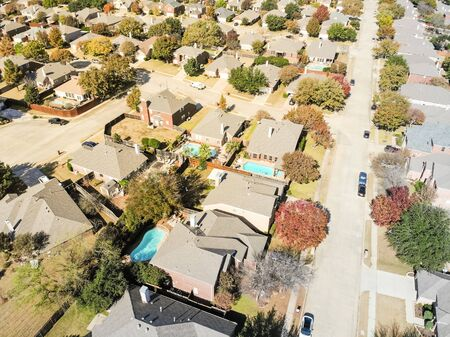 Aerial view of upscale pool houses residential neighborhood in Dallas suburbs with colorful fall foliage. Large detached home permanent dwelling, new roof shingle, a cul-de-sac (dead end) on the left Stockfoto