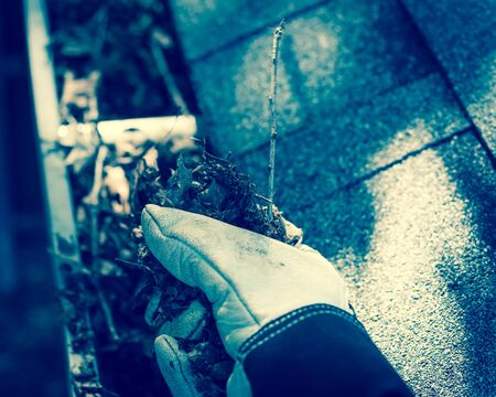 Vintage tone close-up man hand with gloves on ladder cleaning house gutter from leaves and dirt. Roof gutter cleaning near shingles roof in summer time
