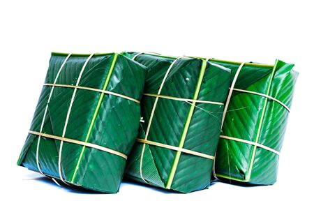Three Chung Cakes isolated on white. Square glutinous sticky rice cake, stuffed with pork meat, green beans, wrapped tied in bamboo leaf and strings. Traditional Vietnamese New Year Tet food