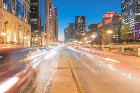 Wacker Dr street with tall buildings and street light trails in Chicago at night Banco de Imagens