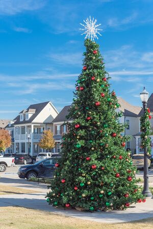 Giant Christmas tree with snowflake tree topper and colorful glass ornaments ball on display at City Square park in Coppell, Texas, USA. Xmas decoration with parked cars and country-style houses Stock Photo