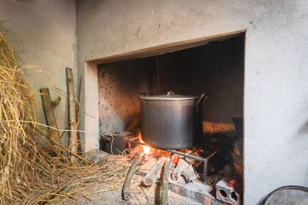 Country kitchen in rural Vietnam with wooden logs, straw and traditional stove. Rarely use huge pot for boiling Vietnamese Chung Cake on Tet Lunar New Year. Ancient and rustic Asian fire pit.