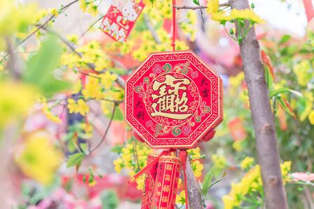 Typical fire crackers hanging on branches of artificial yellow apricot tree at Vietnamese market in Texas, US. Tradition spring flower ornament for home decoration in Tet Lunar New Year festival