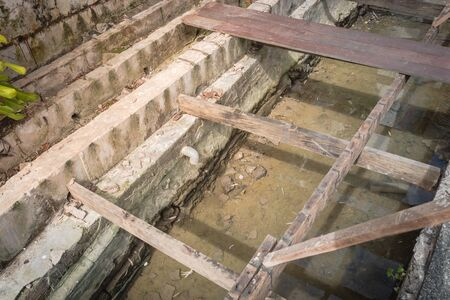 Top view boardwalk remodel along Malacca River, Malaysia. Screw piles under construction with deteriorated and new beams planks platform backwall. Concrete scupper blocks for railings Reklamní fotografie
