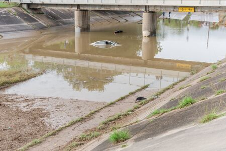 A 15 feet and 9 inches tollway bridge with flooded cars underneath. Swamped sedan vehicles under highway road near downtown Houston, Texas.