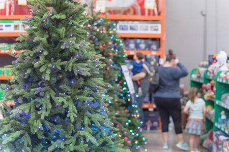 Defocused family members shopping for artificial Christmas tree and toys at home improvement store in USA. Microdot and multi-lights pre-lit Xmas decoration display