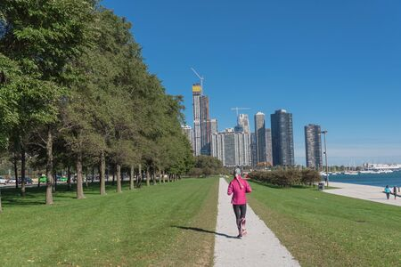Rear view of fitness lady running at downtown park in Chicago along Michigan Lake. Healthy woman in fall sportswear exercise at daytime Reklamní fotografie