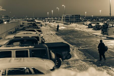 Rear view travelers in warm clothes walking with luggage at terminal parking of Denver International Airport (DIA) in frosty cold autumn sunset. Busy lot with snowdrifts, severe weather condition Reklamní fotografie