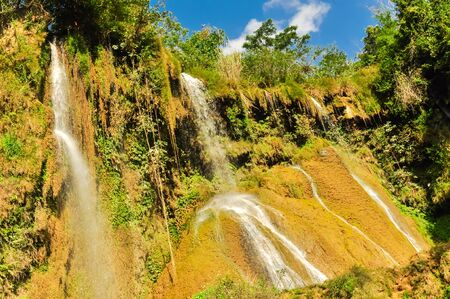 Spectacular view of fall gushes down its slope, white curtain flowing in Dai Yem (Pink Blouse) waterfall, Moc Chau District, Son La Province. Cool refreshing spring pouring on limestone wall, blue cloud sky