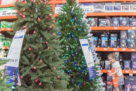 Artificial Christmas tree with label and pre-lit multi color lights, defocused customer shopping in background. Holiday decoration at home improvement store in Texas, America Banco de Imagens