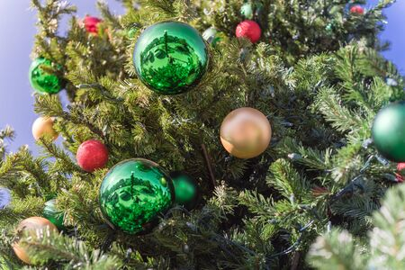 Lookup view of Christmas ball hanging on pine branches at daytime light and blue sky. Baubles and branch of spruce tree. Traditional artificial Xmas ornament at public park near Dallas, Texas Reklamní fotografie