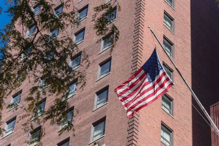 Proudly display of American flag outside of government building near Union Station in downtown Chicago, Illinois. Flying stars and stripes flag with historical brick building facade background