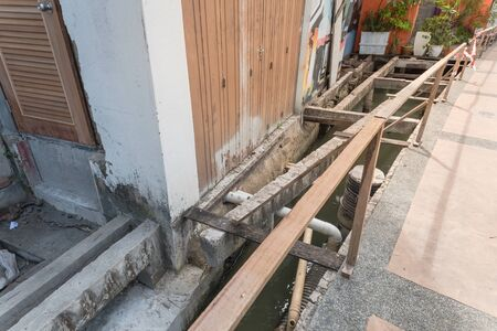 Construction site of patio boardwalk with under deck drainage along Malacca River, Malaysia. Screw piles with deteriorated and new beams planks platform backwall. Concrete scupper blocks railings