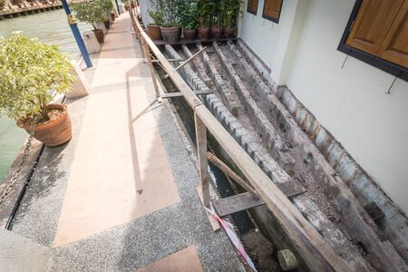 Boardwalk remodel along the bank of Malacca River, Malaysia. Screw piles under construction with deteriorated and new beams planks platform backwall. Concrete scupper blocks for railings