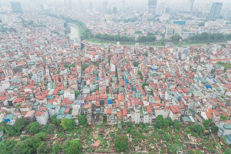 Top view high-density housing surrounding cemetery and To Lich River in Cau Giay District, Hanoi, Vietnam. Hanoi has thousands of high-rise buildings in urban sprawling, foggy day