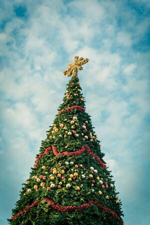 Toned photo of 60 foot Christmas tree with snowflake top, ornament balls and efficient LED lights display at sunset. Typical Xmas decoration at upscale shopping center in Texas, America Banco de Imagens