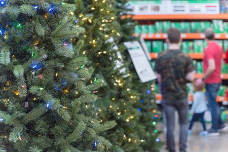 Selective focus on artificial Christmas tree with pre-lit multi color lights and defocused customer shopping in background. Holiday decoration at home improvement store in Texas, America