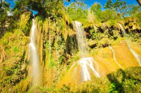 Spectacular view of fall gushes down its slope, white curtain flowing in Dai Yem (Pink Blouse) waterfall, Moc Chau District, Son La Province. Cool refreshing spring pouring on limestone wall, blue cloud sky Foto de archivo - 138396679