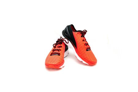 Close-up, top view a pair of brightly red running shoes isolated on white background. New unbranded running shoes, sneaker or training   and copy space. Active and healthy lifestyle.