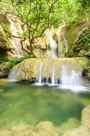 Soft silk stream gushing through cascade tiers into big round limestone rock and emerald pond. Thac Voi waterfall of tropical rainforest in Thanh Hoa province, Vietnam