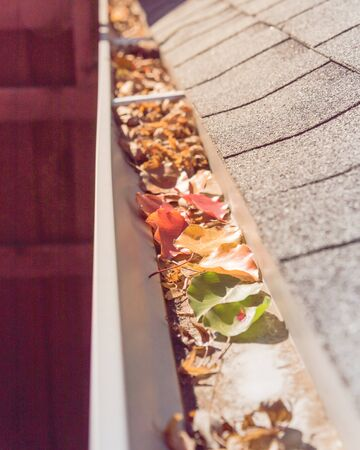 Selective colorful fall foliage of green, yellow, orange, red, dried brown leaves clogged on metal gutter of residential house near Dallas, Texas, USA. Bradford pear leaf crowded on drainage Reklamní fotografie
