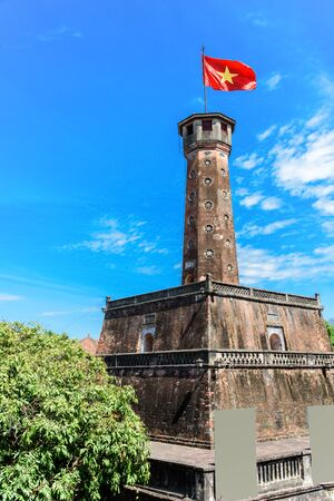 Flag tower with Vietnamese flag on top and empty standing posters. One of the symbols of the city and part of the Hanoi Citadel,  A well known destination for tourist in Vietnam Stock Photo