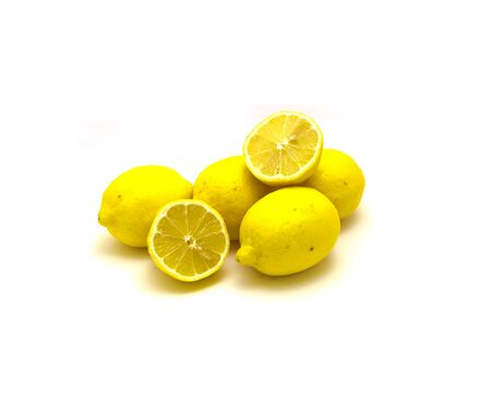 Heap of whole organic ripe lemons with slice cuts isolated on white background. Fresh bright yellow citrus fruit with clipping path and copy space.