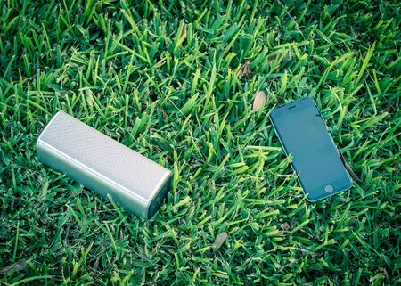 Smart phone and wireless speaker on grass lawn outdoor at sunset. Imagens