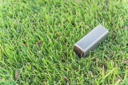Typical wireless speaker on grass lawn at sunset.