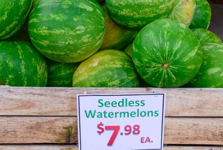 Pile of seedless watermelons in large wooden crate with price tag label in the farmer market at Puyallup, Washington, America. Imagens