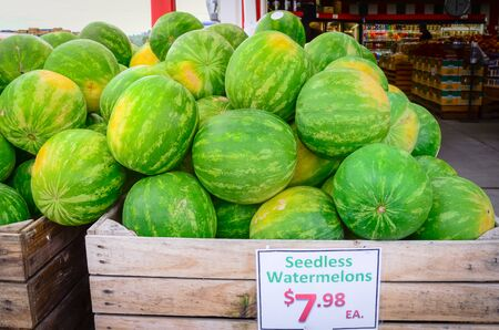 Heap of seedless watermelons in large wooden crate with price tag label at the entrance of local market in Puyallup, Washington, America. Imagens