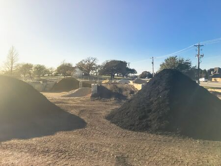 Heap of compost being produced at recycle plant near Dallas, Texas, America. Pile of mulch, sand, gravel, soil, stone, green waste recycling. Sustainability and environment conservation concept