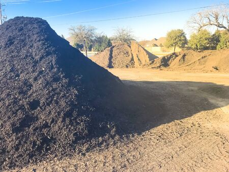 Wholesale compost near highway with large pile of compost, mulch, sand, gravel, soil, stone, green waste recycling. Sustainability and environment conservation concept near Dallas, Texas, USA
