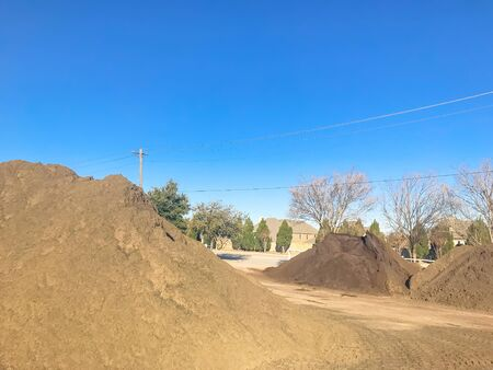 Organic topsoil pile at wholesale compost plant near Dallas, Texas, America. Pile of mulch, sand, gravel, soil, stone, green waste recycling. Sustainability and environment conservation concept