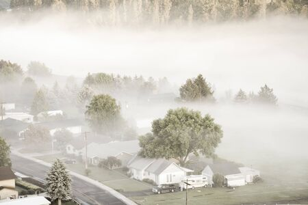 Filtered image of misty spring landscape with foggy and first ray of early morning light. Small valley town at rural of Colfax, Eastern Washington, US surround by morning fog, pine trees and empty road