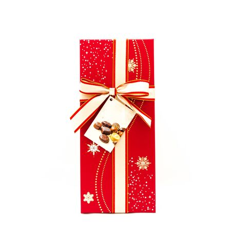 Chocolate box with tab label and red yellow color bow knot isolated on white background. Paper gift box with ribbon tie for valentine day package concept Banco de Imagens