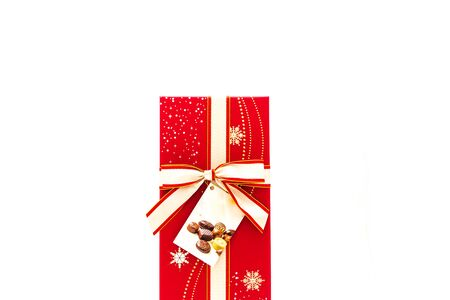 Red chocolate box with tag label and red yellow bow ribbon isolated on white