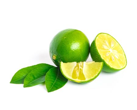One whole raw lime with slice cutout and green leaves isolated on white background. Fresh picked Asian lemon with clipping path and copy space.