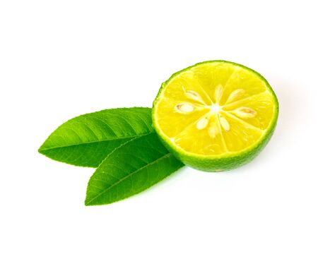 Half cut of Asian lime with green leaves isolated on white background. Fresh picked Asian lemon with clipping path and copy space. Banco de Imagens