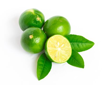 Three whole raw limes with slice cutout and green leaves isolated on white background. Fresh picked Asian lemon with clipping path and copy space.