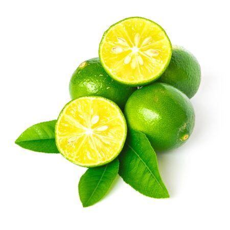 Pile of raw limes with half cuts slices and green leaves isolated on white background. Fresh picked Asian lemon with clipping path and copy space. Banco de Imagens