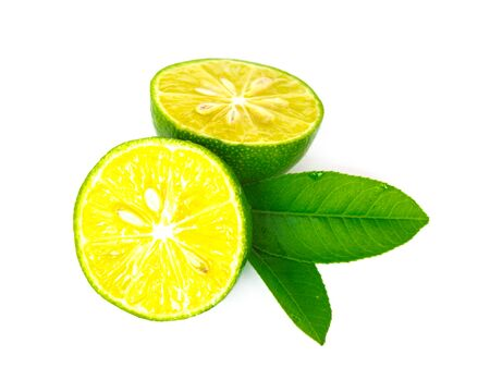 Two half cuts of Asian limes with green leaves isolated on white background. Fresh picked Asian lemon with clipping path and copy space.