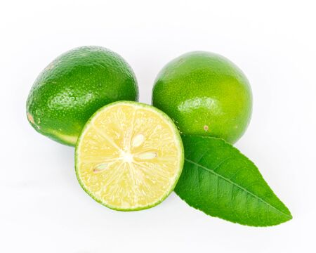 Two whole raw limes with half cut slices and green leaves isolated on white background. Fresh picked Asian lemon with clipping path and copy space.