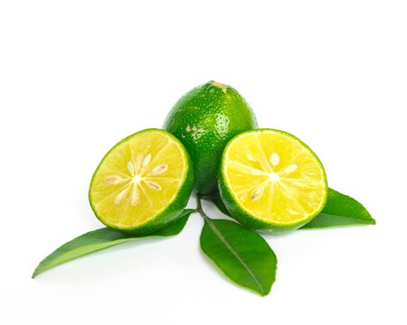 Small lime leaves branch with whole fruit and two half cut isolated on white. Fresh picked homegrown Asian lemon with clipping path and copy space. Banco de Imagens