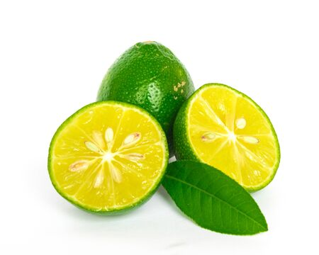 One whole raw lime with two half cuts and green leaves isolated on white background. Fresh picked Asian lemon with clipping path and copy space.